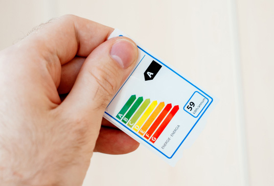 Energy efficiency label sticker used for household appliances and electrical devices in man hand